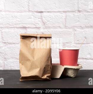 red paper disposable cups stand in the tray, white background, takeaway containers. - Stock Photo