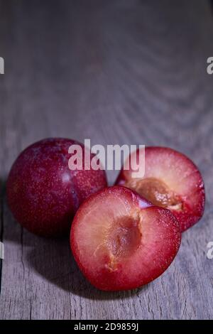 Plums on barnwood - Stock Photo