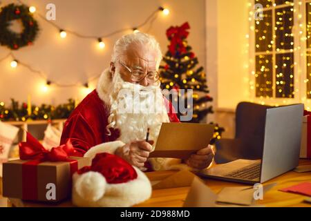 Santa Claus Desk Reading Wish List With Ornament And Christmas Gift Stock Photo Alamy