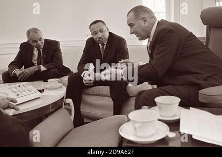 Roy Wilkins and Dr. Martin Luther King, Jr. meet with President Lyndon B. Johnson in the Oval Office of the White House on January 18, 1964. - Stock Photo