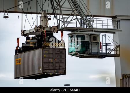 Crane loading and unloading shipping containers on a train in the Vienna Danube port area