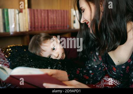 A young woman reads a book to a child. A mother teaches her little boy to read. Stock Photo