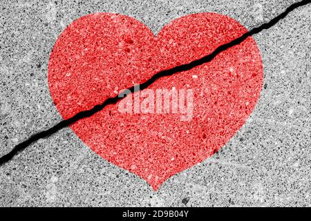 Red heart on a cracked texture. The concept of broken heart, end of love and disappointment.