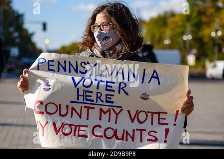 Germany, Berlin, November 04, 2020: A protesters and supporters of Democratic presidential candidate former Vice President JOE BIDEN holding a sign reading 'Pennsylvania Voter here Count my vote! my vote counts!'' can be seen next to the Brandenburg Gate in Central Berlin during a rally unter the motto 'Count the Votes! Rally for Fair Elections in the USA' organized by the Democrats Abroad, the official organization of the Democratic Party for United States citizens living permanently or temporarily outside the United States, during the pending final vote count for the 2020 United States presi - Stock Photo