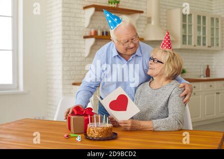 Happy loving senior couple in party hats having quiet birthday celebration at home