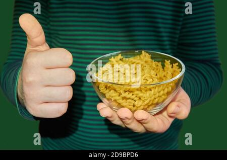 The child holds a glass plate with pasta in his left hand, and shows Like with his right hand.