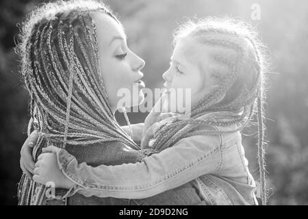 Family and motherhood concept. Mother and child girl playing kissing and hugging. Little daughter hugging her happy mother.