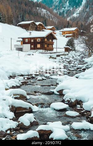 Ice and snow covered creek on a cold winter day infront of traditional wooden cabins of little mountain village St. Gertraud in Ultental, South Tyrol/ - Stock Photo