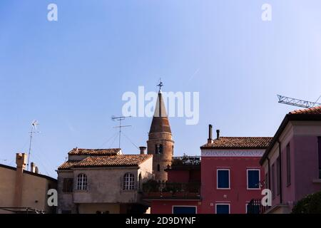 Protruding bell tower behind buildings with blue sky in the background. Caorle Italy