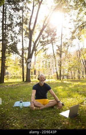 Joyful male doing practice in nature online