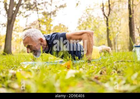 Mature bearded male doing push ups in nature