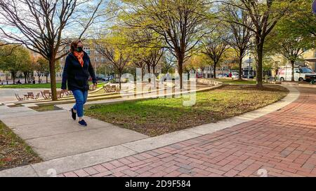 Reston, VA, USA — Nov 3, 2020.  A wide angle photo of a woman taking a walk in Reston Town Center Park on an Autumn afternoon.