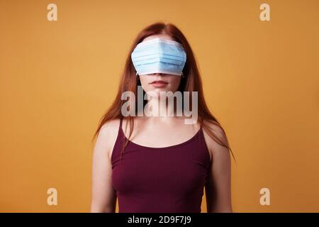 young woman wearing medical face mask over her eyes - funny corona denier concept