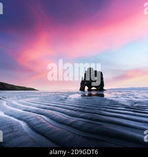 Basalt stack Hvitserkur on the Vatnsnes peninsula, Iceland, Europe in low tide time. Great purple sky glowing on background. Landscape photography - Stock Photo