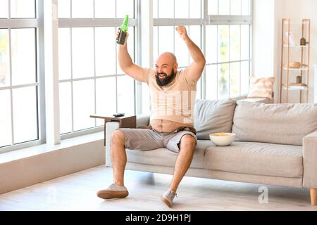 Lazy overweight man with beer and chips watching TV at home