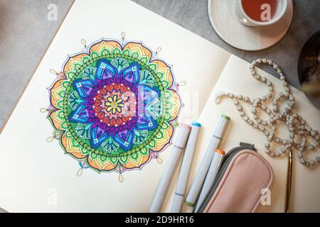 Top view of colored mandala art book with colorful markers, pen, pink pen case and rosary beads. - Stock Photo
