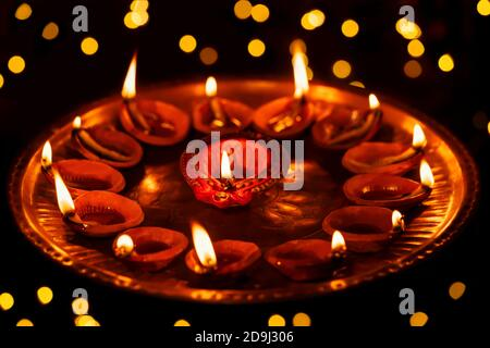 Clay diya oil lamps burning, lit or illuminated on Diwali night in dark bokeh background at home. Concept for Indian Hindu festival celebration.