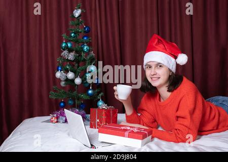 A young woman in a Santa hat and a red sweater holds a mug of coffee or tea, rests with her laptop, lying on the bed, surrounded by Christmas gifts. - Stock Photo