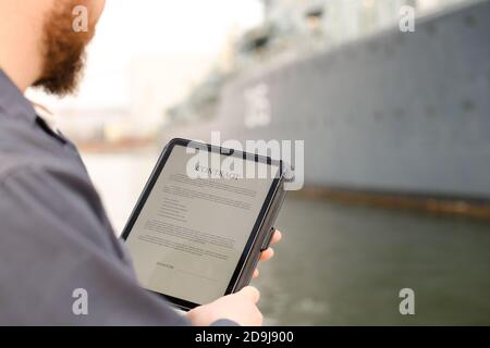 Marine engineer reading contract on tablet near vessel in background.