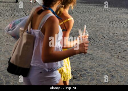 Two teenage girls carrying plastic cups with straws in Piazza Santa Maria, Trastevere, Rome, Italy. - Stock Photo