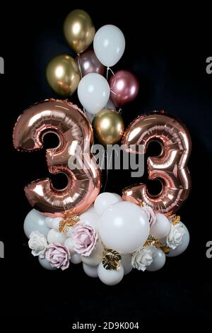 birthday card. Congratulations to 33 years old. Composition of balls and flowers on a black background. - Stock Photo