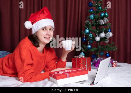 A young woman in a Santa hat and a red sweater holds a mug of coffee or tea, rests with her laptop, lying on the bed, surrounded by Christmas gifts. C - Stock Photo