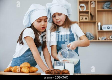 Two little girls in blue chef uniform pouring milk into glasses on the kitchen with cookies on table - Stock Photo
