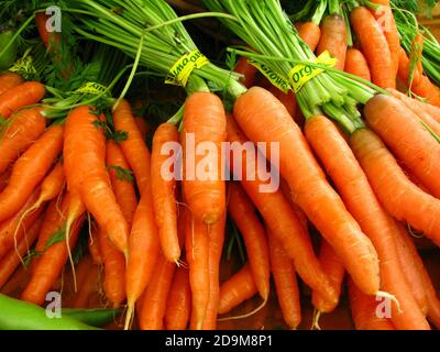 Closeup shot of fresh bundles of carrots with yellow tape displayed in a grocery