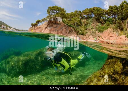 Split level shot of diving on house reef in Tamariu, Costa Brava, Spain, Mediterranean - Stock Photo