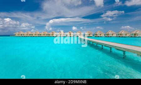 Panoramic landscape of Maldives beach. Tropical panorama, luxury water villa resort with wooden pier or jetty. Luxury travel destination background