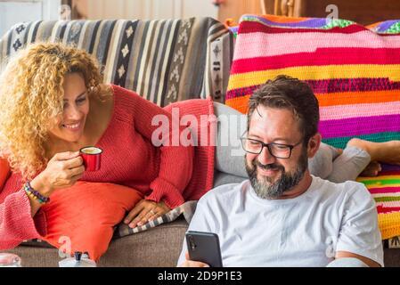 Cheerful adult couple enjoy time together at home having breakfast in the morning - wake up in real life with happy caucasian people - concept of share life for young mature man and woman in coloured interior house