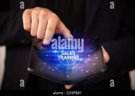 Businessman holding a foldable smartphone with SALES TRAINING inscription, new business concept