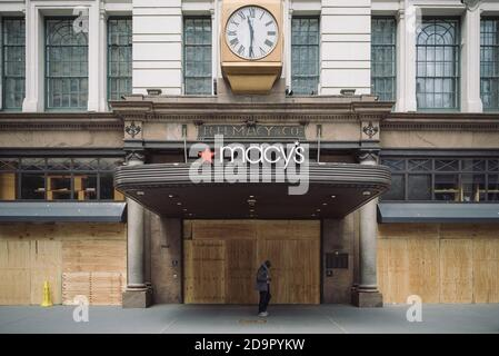 A man walks in front of closed and boarded up Macy's main entrance in Midtown. - Stock Photo