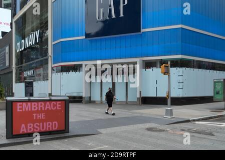 A man wearing a mask walks in front of a closed and boarded up Gap store in Times Square. - Stock Photo