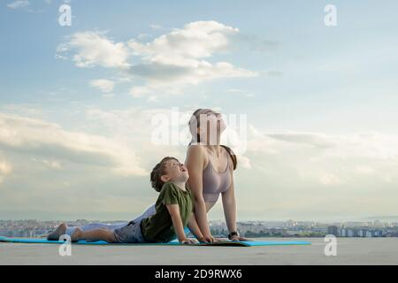 Mother and son doing exercise on the balcony in the background of a city during sunrise or sunset, concept of a healthy lifestyle