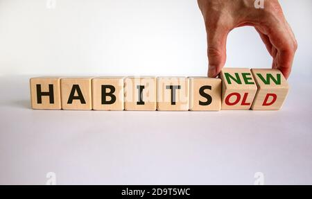 Male hand turning a cube and changes the expression 'old habits' to 'new habits'. Beautiful white table, white background. Concept. Copy space. - Stock Photo