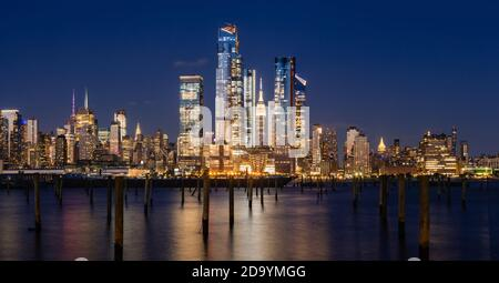 New York City evening panoramic of Manhattan Midtown West skyline with illuminated Hudson Yards skyscrapers from the Hudson River. NYC, USA