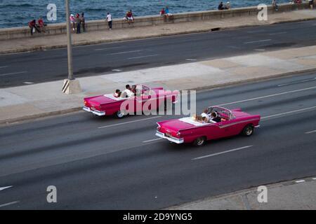Two similar classic cars racing along by the Macedon, from the Hotel Nacional, Havana,  Cuba