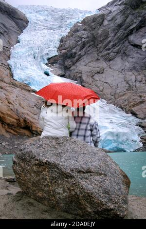 Briksdal Glacier (Briksdalbreen), Norway. Couple with an umbrella sitting on a rock looking at Briskdal Glacier. View of the glacier 10 years ago.