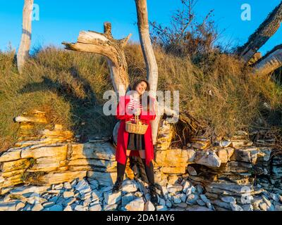 Young woman aka little Red Riding Hood with pastoral wicker basket in hand standing happy smiling looking away aside - Stock Photo