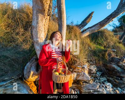 Young woman aka little Red Riding Hood with pastoral wicker basket in hand standing apple in hand looking away aside upwards up daydreaming dreamy - Stock Photo