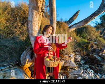 Young woman aka little Red Riding Hood with pastoral wicker basket in hand standing going to eat wants want apple in hand looking away aside happy - Stock Photo
