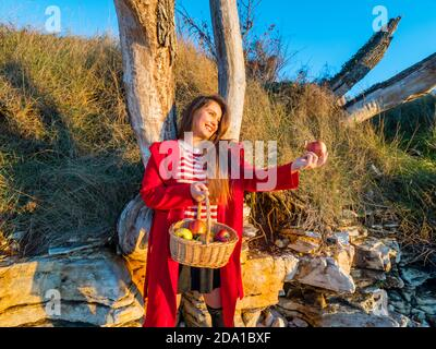 Young woman aka little Red Riding Hood with pastoral wicker basket standing apple in hand looking away aside happy smiling laughing - Stock Photo