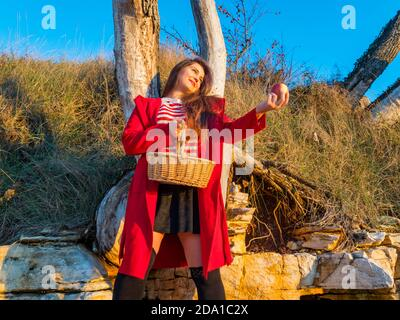 Young woman aka little Red Riding Hood with pastoral wicker basket standing apple in hand looking away aside happy smiling - Stock Photo