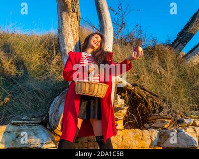 Young woman aka little Red Riding Hood with pastoral wicker basket  standing apple in hand happy smiling laughing - Stock Photo