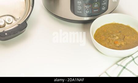 Creamy lentil soup cooked in multi cooker close up in a bowl on white background with copy space - Stock Photo