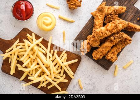 Fish and chips. Deep fried fish filet and with french fries on white background with sauces. Traditional british street food.