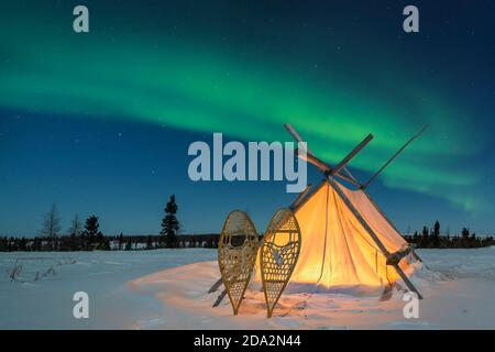 Trappers tent with snowshoes and nightsky with Aurora borealis, Northern lights, Wapusk National Park, Manitoba, Canada - Stock Photo