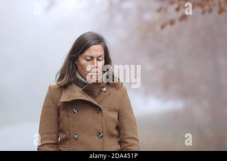 Sad middle age woman looking down walking in a forest in autumn a foggy day