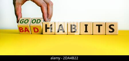 Male hand turning cubes and changes the expression 'bad habits' to 'good habits'. Beautiful yellow table, white background. Concept. Copy space. - Stock Photo